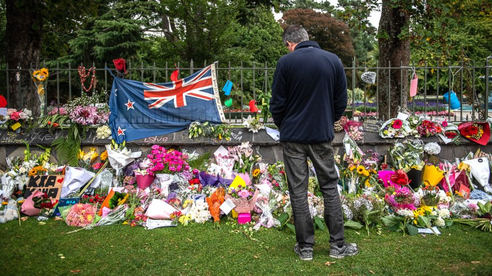 A man pauses next to a New Zealand flag hung amongst flowers and tributes on the wall of the Botanic Gardens, March 17, 2019, in Christchurch, New Zealand for the victims of a mass shooting at two mosques.