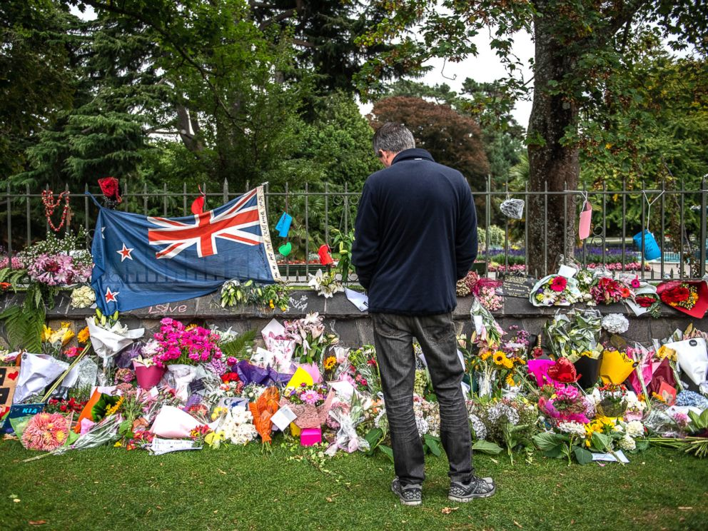 PHOTO: A man pauses next to a New Zealand flag hung amongst flowers and tributes on the wall of the Botanic Gardens, March 17, 2019, in Christchurch, New Zealand for the victims of a mass shooting at two mosques.