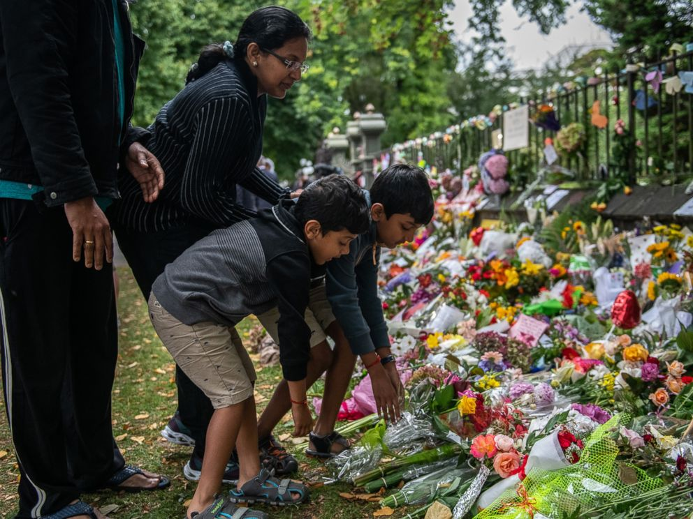 PHOTO: A family lay flowers by the wall of the Botanic Gardens, March 17, 2019 , in Christchurch, New Zealand after a mass shooting at two mosques.
