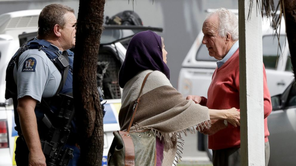 People wait outside a mosque in central Christchurch, New Zealand, Friday, March 15, 2019.