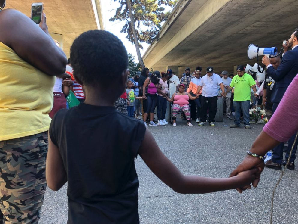 People hold hands during a vigil for Nia Wilson outside the MacArthur Bay Area Rapid Transit station, in Oakland, Calif., July 23, 2018.