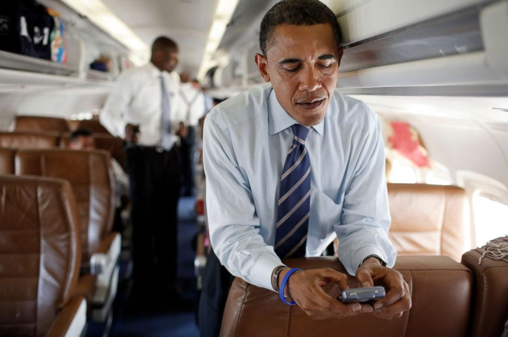 PHOTO: Presidential candidate Senator Barack Obama works his cellphone on his campaign plane at Reagan National airport on July 9, 2008 in Washington, DC..