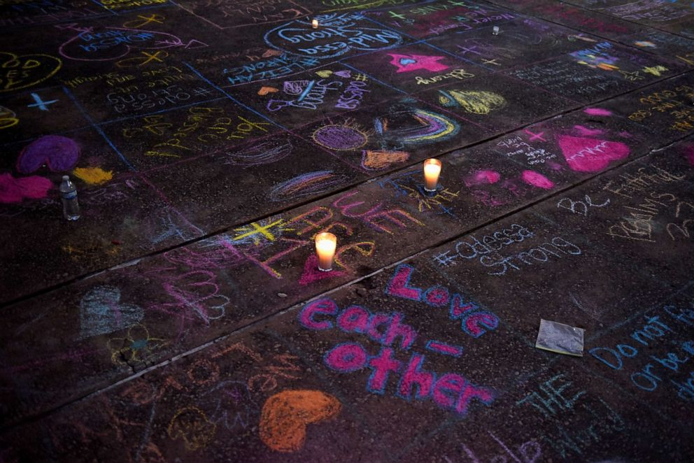 PHOTO: Messages written in sidewalk chalk are seen as people gather for a vigil following Saturdays shooting in Odessa, Texas, on Sept. 1, 2019.