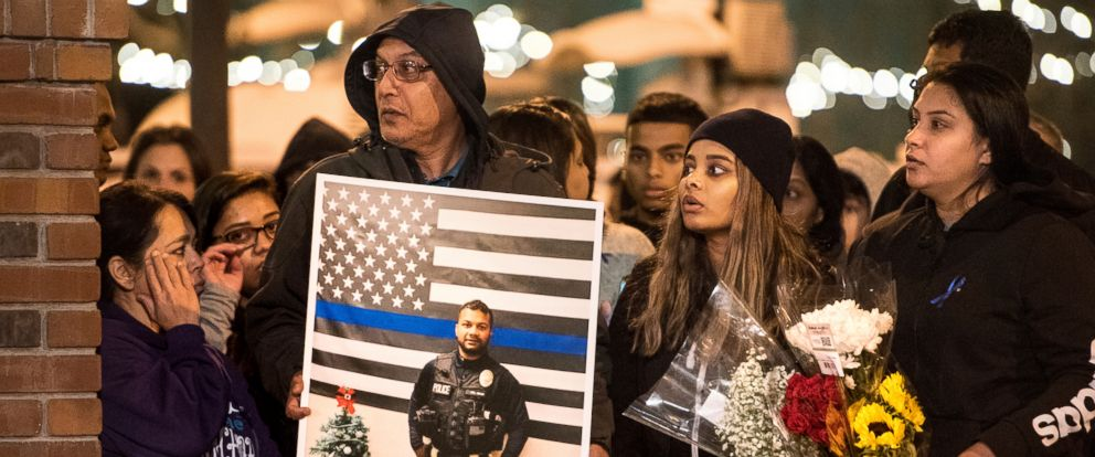 PHOTO: Family members of police Cpl. Ronil Singh including Birend Singh, holding picture at left, attend a candlelight vigil for the slain officer in downtown Newman, Calif., Dec. 28, 2018.