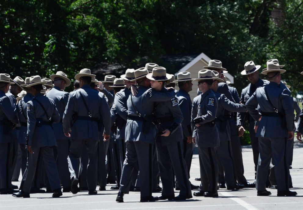 PHOTO: New York State Police Troopers embrace before leaving the funeral service for fellow Trooper Nicholas F. Clark, July 8, 2018, at Alfred University in Alfred, N.Y.