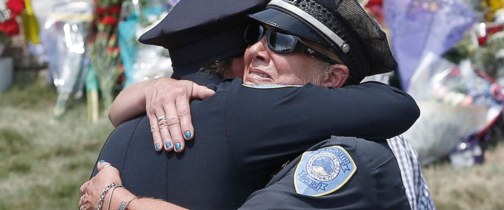 PHOTO: Weymouth Police officers embrace after the procession for slain Weymouth Police officer Michael Chesna, 42, passed by the Weymouth Police station in Weymouth, Mass., July 16, 2018.