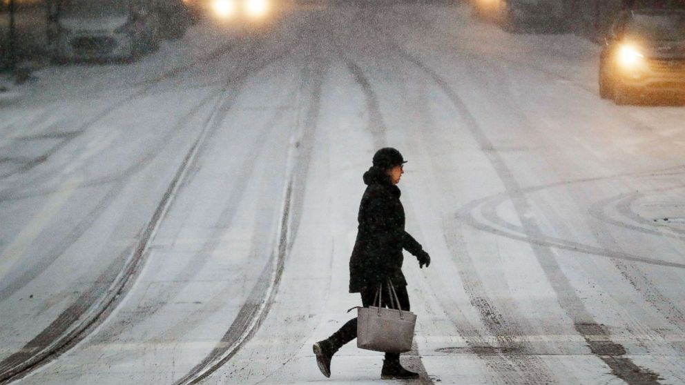 A commuter braves the wind and snow in frigid weather, Jan. 30, 2019, in Cincinnati.