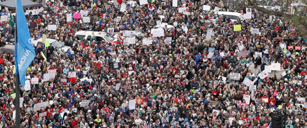 PHOTO: A crowd listens to speakers on a stage, lower right, during a teacher rally to protest low student funding at the state Capitol in Oklahoma City, April 2, 2018.