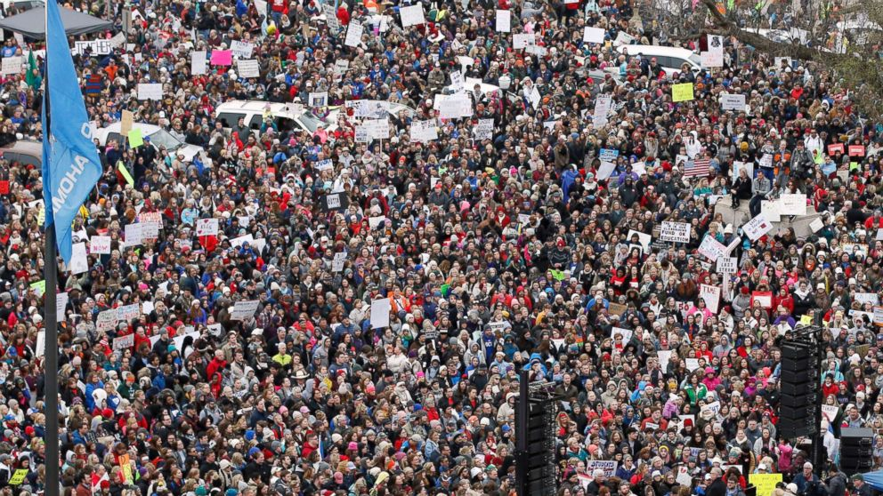 A crowd listens to speakers on a stage, lower right, during a teacher rally to protest low student funding at the state Capitol in Oklahoma City, April 2, 2018.
