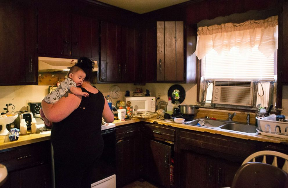 PHOTO: Deborah Crowder holds her grandson Jaydain while she cooks dinner for her family.