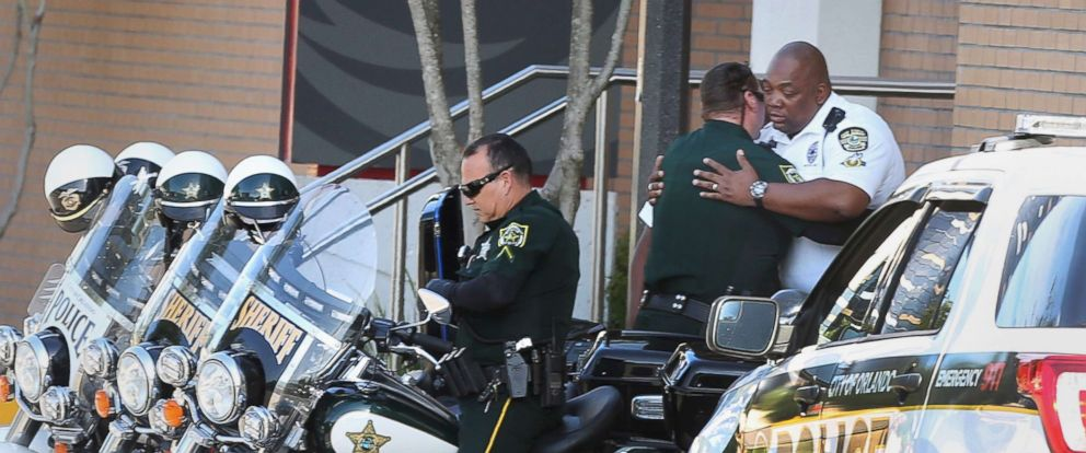 PHOTO: A Orange County Sheriff motor deputy, center, consoles Orlando Police motor officer, right, at Orlando Regional Medical Center after a OPD officer was shot and severely injured while responding over night to a domestic dispute call, June 10, 2018.