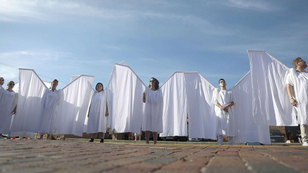 People dressed as angels stand in front of the memorial set up for the shooting victims at Pulse nightclub where the shootings took place two years ago, June 12, 2018, in Orlando, Fla.