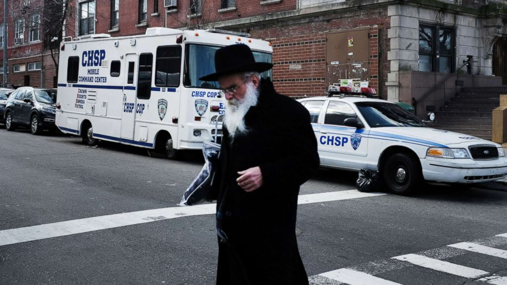 An Orthodox Jewish man walks past a security vehicle in the neighborhood of Crown Heights, Feb. 25, 2019, in New York City.