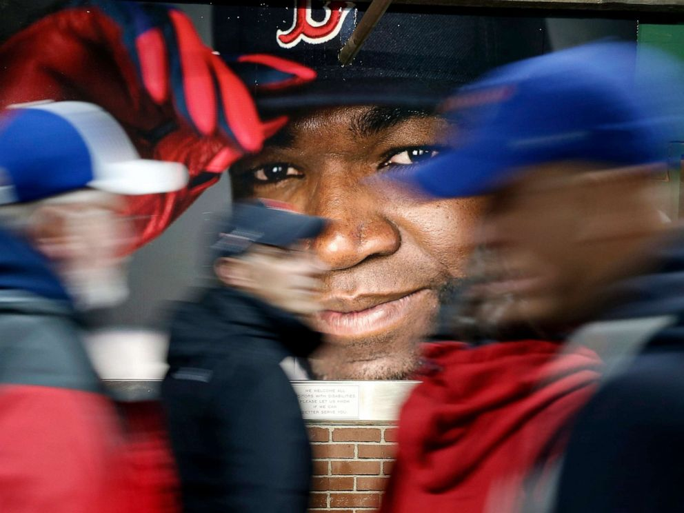 PHOTO: Fans at walk past a photograph of Boston Red Soxs David Ortiz before a baseball game at Fenway Park in Boston, Oct. 1, 2016.