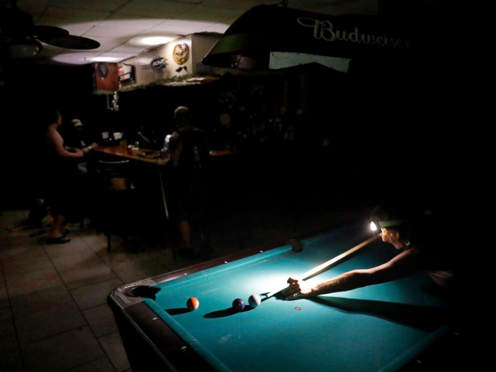 PHOTO: Lisa Borruso plays pool using a headlamp as the power remains out following Hurricane Irma at Gators Crossroads in Naples, Fla., Sept. 11, 2017.