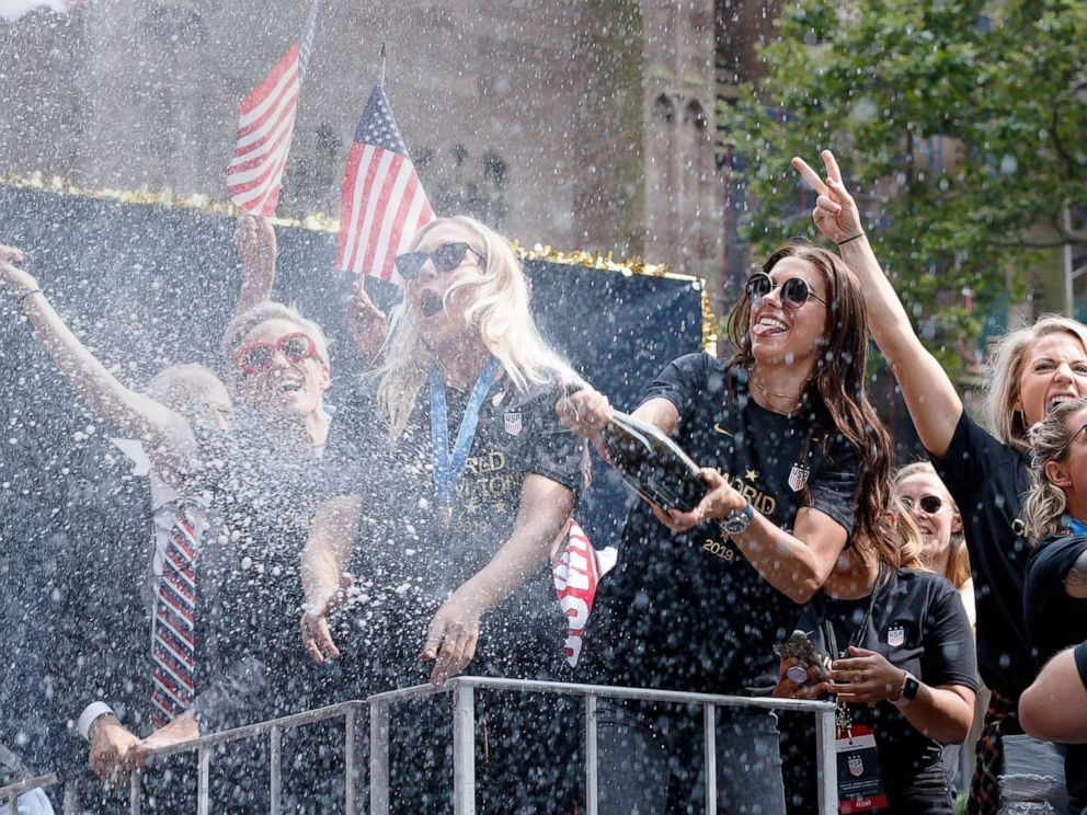 PHOTO: U.S. Womens soccer player Alex Morgan sprays champagne into the crowd during a ticker tape parade celebrating the teams 2019 World Cup victory in New York City, July 10, 2019.