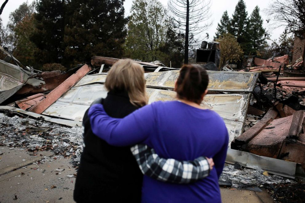 Two neighbors comfort each other in front of the remains of a home after the two returned for the first time since the Camp Fire in Paradise, Calif., Nov. 22, 2018.