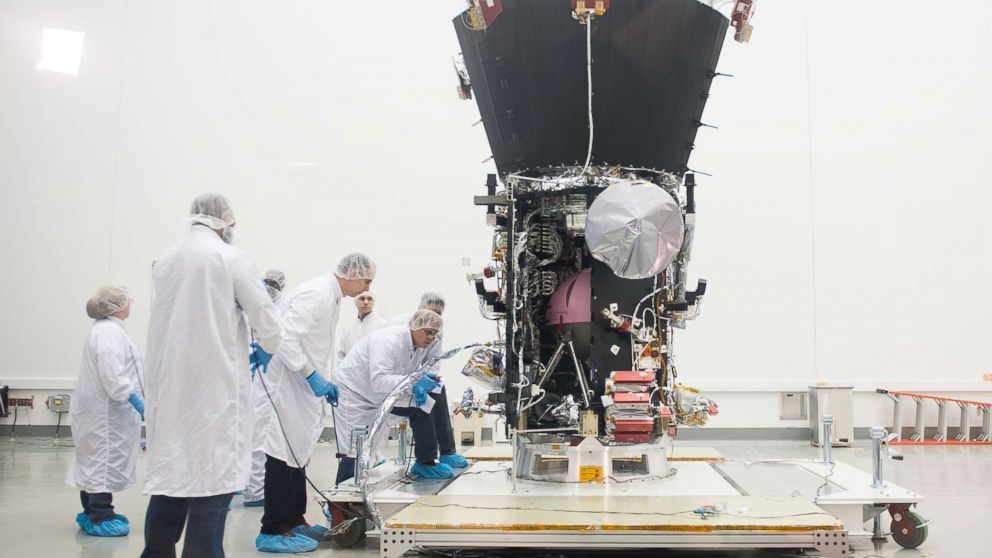 Engineers examine the Parker Solar Probe during a media preview at NASA Goddard Space Flight Center in Greenbelt, Md., March 28, 2018. The spacecraft is undergoing final testing before it ships to NASAs Kennedy Space Flight Center in Florida for a scheduled July 31 launch when it will travel on a daring trek, traveling closer to the Sun than any spacecraft in history.