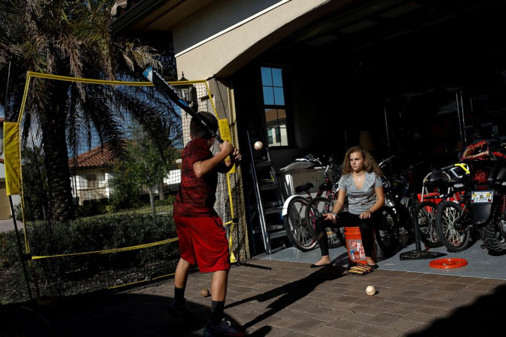 PHOTO: Daniela Menescal, who was injured by shrapnel during the mass shooting at Marjory Stoneman Douglas High School, helps her brother practice baseball at their house in Parkland, Florida, April 4, 2018.