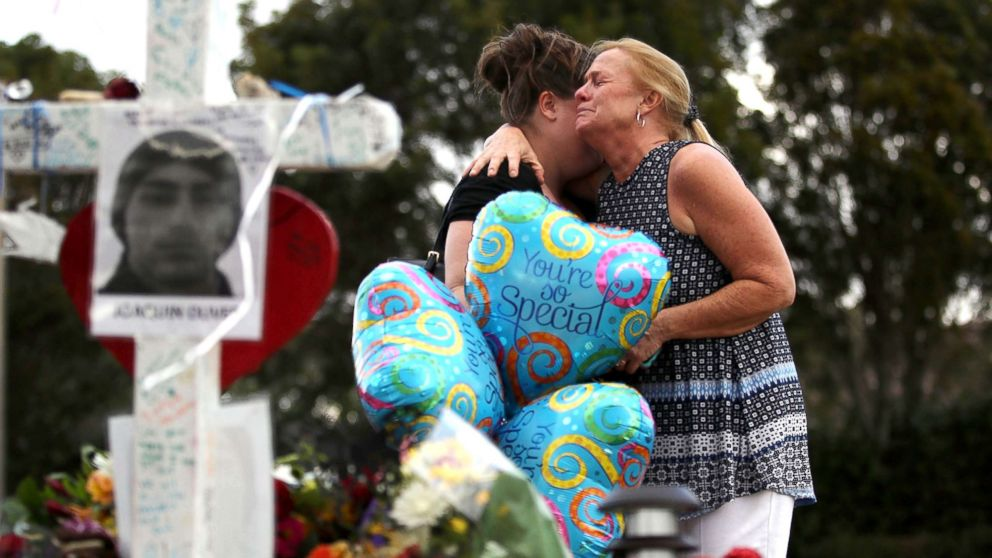 Cindy Sotelo (R) cries with her daughter, Jessica Malone, an alumna of Marjory Stoneman Douglas High School, as they visit a makeshift memorial setup in front of the school, Feb. 19, 2018 in Parkland, Fla.