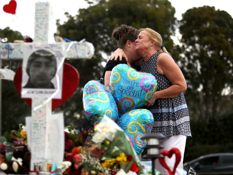 PHOTO: Cindy Sotelo (R) cries with her daughter, Jessica Malone, an alumna of Marjory Stoneman Douglas High School, as they visit a makeshift memorial setup in front of the school, Feb. 19, 2018 in Parkland, Fla.