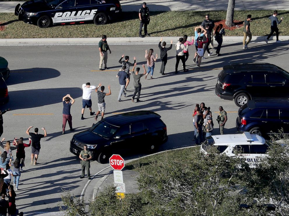 PHOTO: Students hold their hands in the air as they are evacuated by police from Marjory Stoneman Douglas High School in Parkland, Fla., Feb. 14, 2018, after a shooter opened fire on the campus.