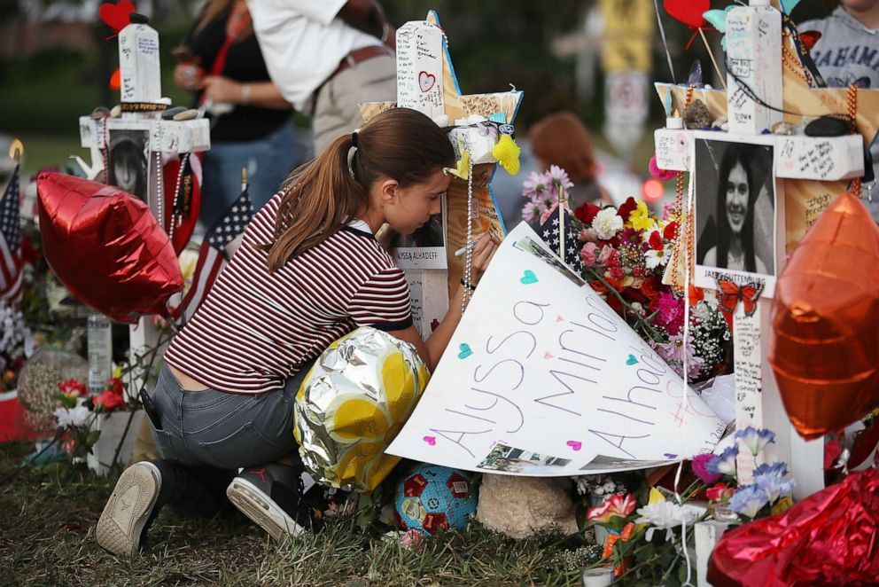 PHOTO: Victoria Seltzer writes a passage on a cross setup in a makeshift memorial in front of Marjory Stoneman Douglas High School in memory of the 17 people that were killed in a mass shooting, Feb. 21, 2018 in Parkland, Fla.
