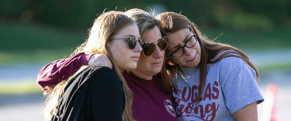 PHOTO: From left, Emma Rothenberg, her mother Cheryl Rothenberg and sister, Marjory Stoneman Douglas High School student Sophia Rothenberg embrace at a memorial marking the one-year anniversary of a shooting at the school in Parkland, Fla., Feb. 14, 2019.