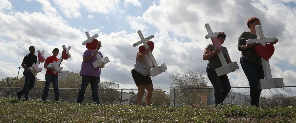 PHOTO: Volunteers carry crosses to be placed in front of the Marjory Stoneman Douglas High School, Feb. 18, 2018 in Parkland, Fla.