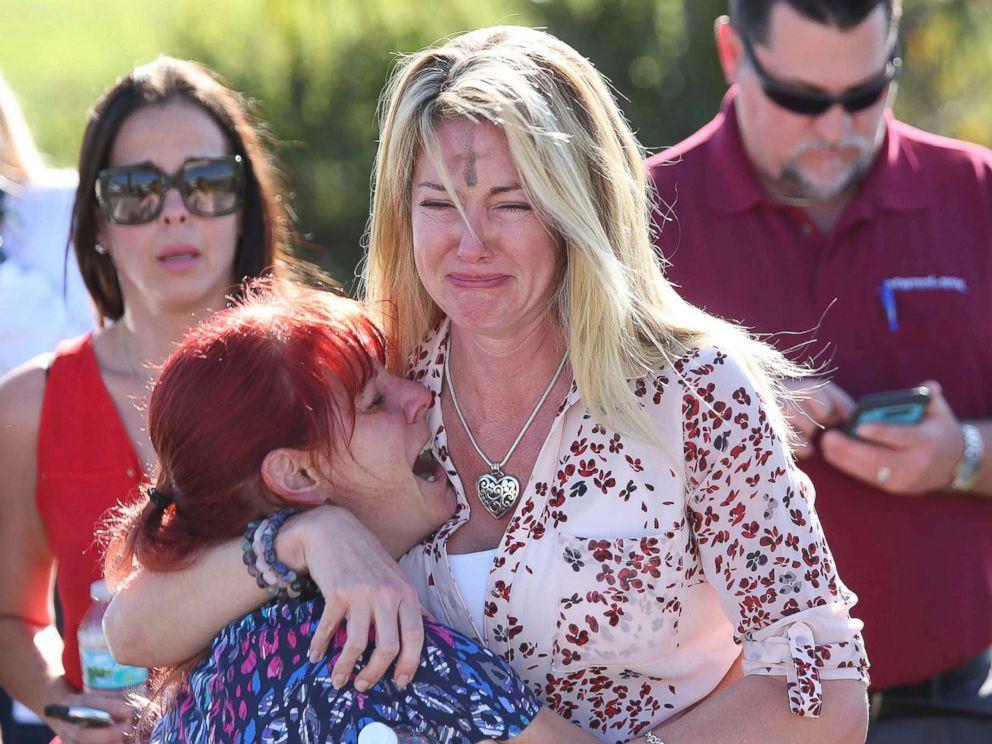 PHOTO: Des femmes s'embrassent dans une salle d'attente pour les parents d'élèves après une fusillade à l'école secondaire Marjory Stoneman Douglas à Parkland, en Floride, le 14 février 2018.
