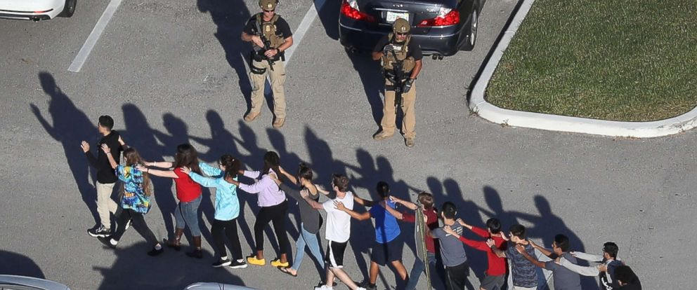 PHOTO: People are brought out of the Marjory Stoneman Douglas High School after a shooting at the school on Feb. 14, 2018 in Parkland, Fla.