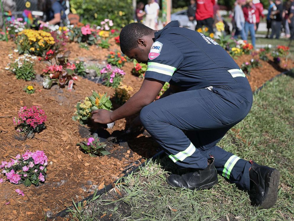 PHOTO: Devon Fuller places a plant in the ground at a garden setup in memory of those lost a year ago during a mass shooting at Marjory Stoneman Douglas High School, Feb. 14, 2019 in Parkland, Fla.