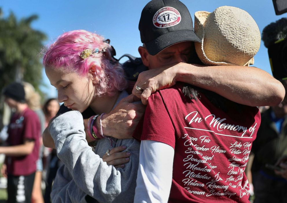 PHOTO: Anthony Gonzalez hugs his daughter, Victoria Gonzalez and her teacher Ronit Reoven, right, as they visit a memorial setup near Marjory Stoneman Douglas High School, Feb. 14, 2019 in Parkland, Fla.
