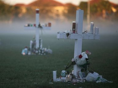 PHOTO: Candles that were placed on crosses still glow after last nights vigil for victims of the mass shooting at Marjory Stoneman Douglas High School, at Pine Trail Park, Feb. 16, 2018, in Parkland, Fla.