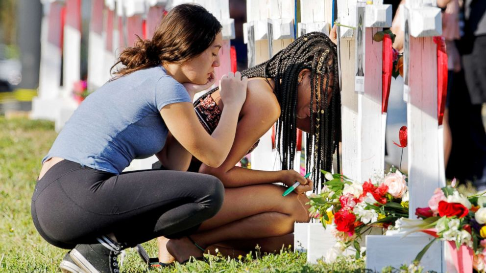 A senior at Marjory Stoneman Douglas High School weeps in front of a cross and Star of David for shooting victim Meadow Pollack while a fellow classmate consoles her at a memorial by the school in Parkland, Fla., Feb. 18, 2018.