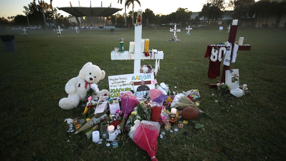 Flowers and mementos are placed on a memorial site, Feb. 17, 2018, for those killed mass shooting at Marjory Stoneman Douglas High School, in Parkland, Fla.