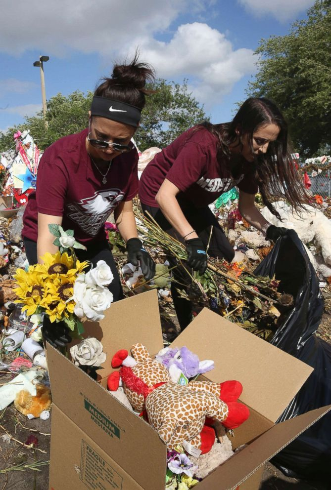 PHOTO: Rachel Polakoff and Lenzai Cutler remove items from the memorial site for the victims of the Marjorie Stoneman Douglas High School shooting in Parkland, Fla., March 29, 2018.