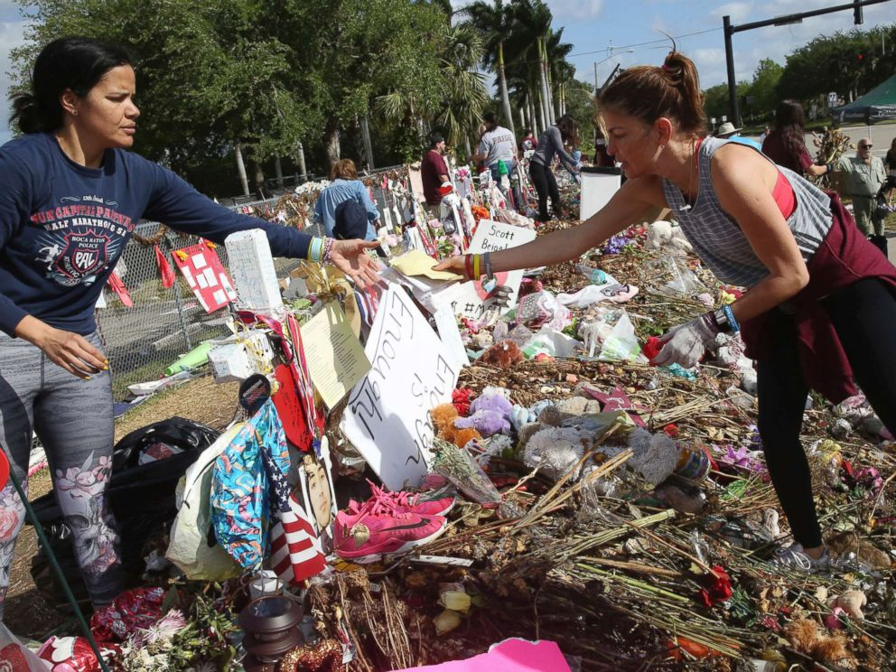 PHOTO: Patricia Padauy, right, passes a handwritten note to her friend Sharamy Angarita, as they clean and sort out items at the memorial site of Padauys son Joaquin Oliver in Parkland, Fla., March 28, 2018.