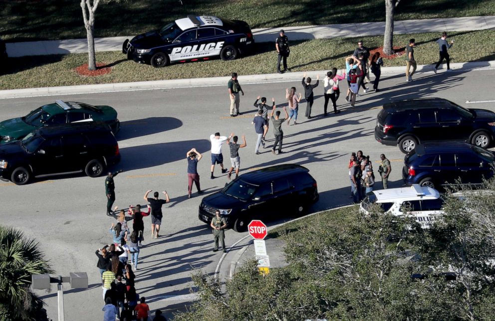 PHOTO: Students hold their hands in the air as they are evacuated by police from Marjory Stoneman Douglas High School in Parkland, Fla., after a shooter opened fire on the campus, Feb.14, 2018.