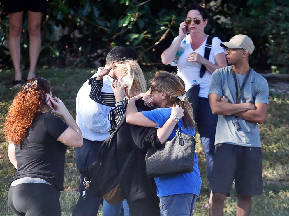 PHOTO: Anxious family members wait for news of students as two people embrace, Feb. 14, 2018, in Parkland, Fla.