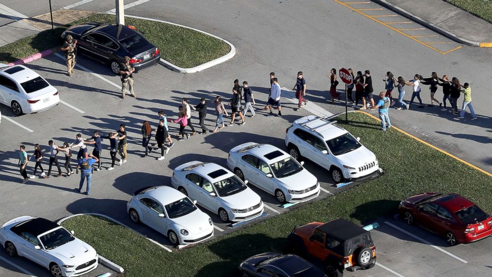 People are brought out of the Marjory Stoneman Douglas High School after a shooting, Feb. 14, 2018, in Parkland, Florida.