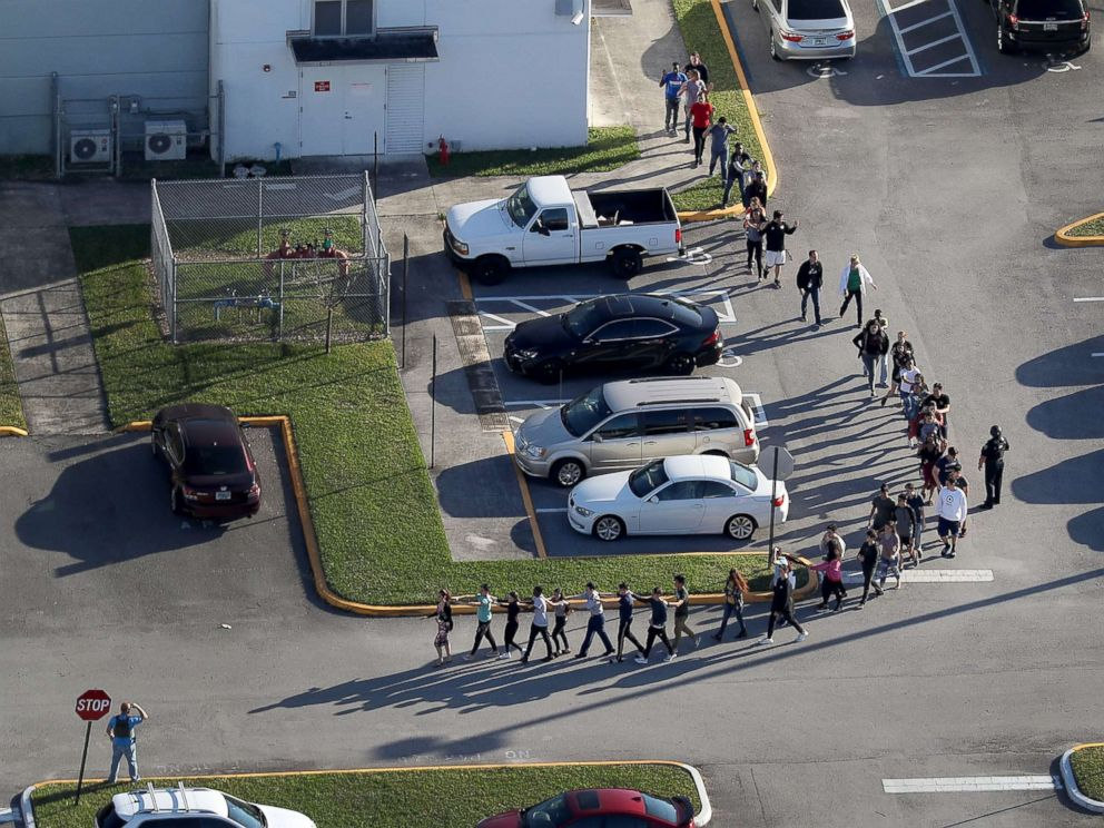 PHOTO: People are brought out of the Marjory Stoneman Douglas High School after a shooting, Feb. 14, 2018, in Parkland, Florida.