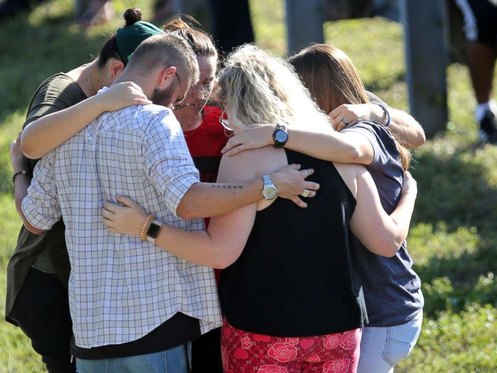 PHOTO: People bow their heads while waiting for word from students at Stoneman Douglas High School in Parkland, Fla., after a shooting on Feb. 14, 2018.