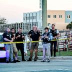 A group of police officers stand guard in front of the side entrance of the Marjory Stoneman Douglas High School after a shooting in Parkland, Fla., Feb. 14, 2018.