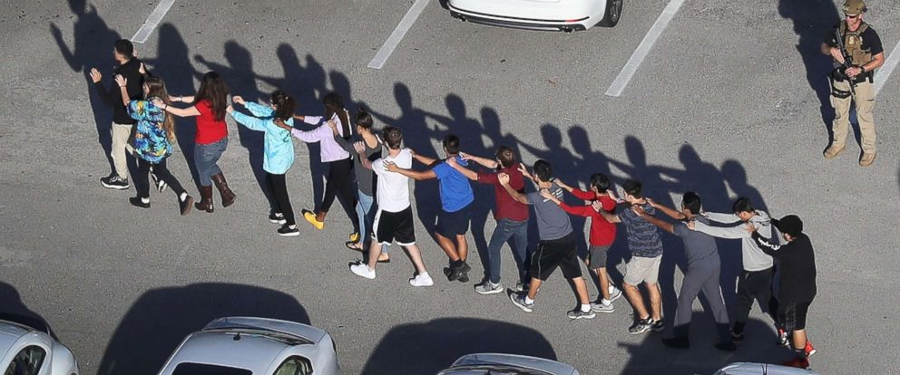 PHOTO: People are brought out of the Marjory Stoneman Douglas High School after a shooting at the school, Feb. 14, 2018, in Parkland, Fla.