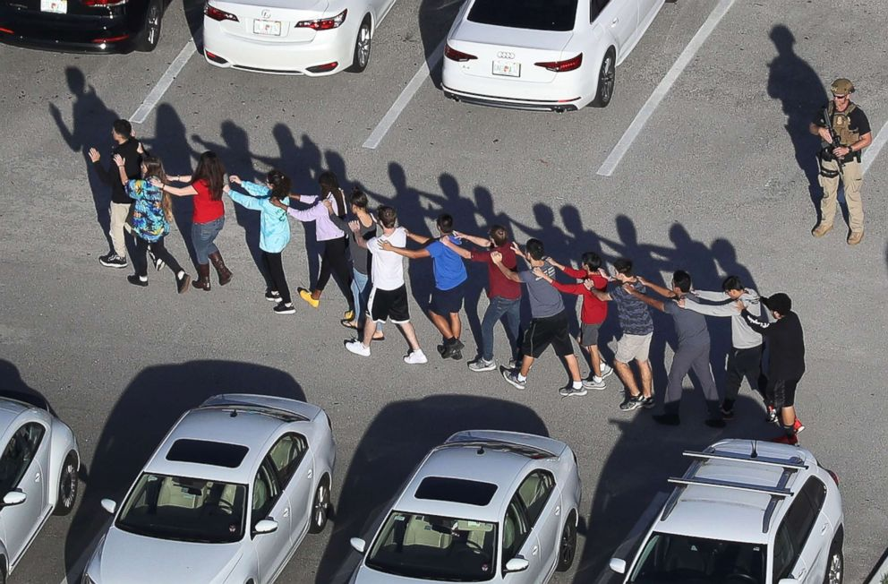 Students are brought out of the Marjory Stoneman Douglas High School after a shooting at the school on Feb. 14, 2018, in Parkland, Fla.