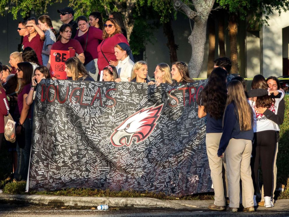 PHOTO: A banner bearing messages is held as parents and students arrive at Marjory Stoneman Douglas High School in Parkland, Fla., Feb. 28, 2018, for the schools reopening, two weeks after the mass shootings at the school.