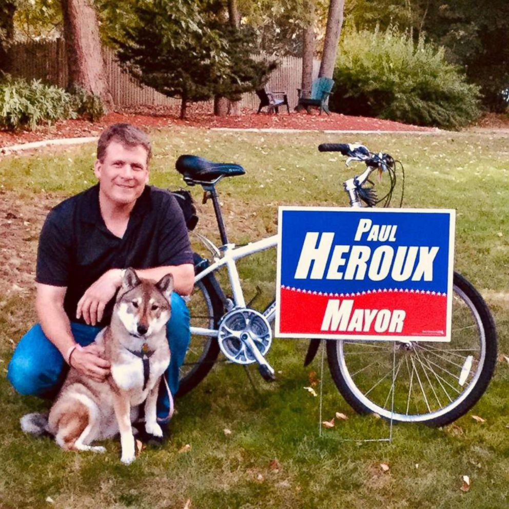 Paul Heroux sits by a campaign sign with Mura in an undated handout photo.