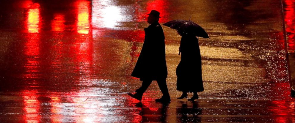 PHOTO: Pedestrians are silhouetted against wet pavement as they walk in Kansas City, Mo., Dec. 26, 2018.