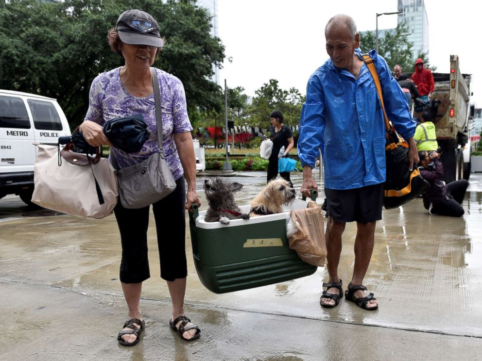 PHOTO: A couple of evacuees carry their dogs into the the George R. Brown Convention Center after Hurricane Harvey inundated the Texas Gulf coast with rain causing widespread flooding, in Houston, Aug. 27, 2017.